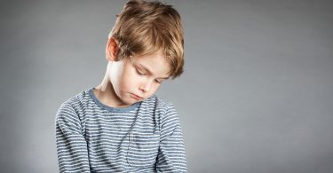 young-boy-looking-sad-in-striped-shirt