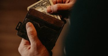 man-holding-wallet-with-money